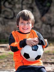 Gluecklicher Junge mit Torwart Trikot und Ball