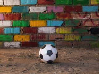 Fussball vor einer bunten Ziegelsteinwand