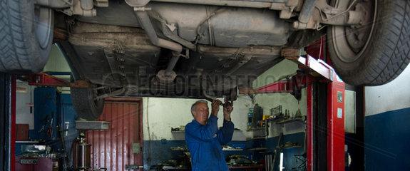 Posen  Polen  ein KFZ-Mechaniker arbeitet am Unterboden eines Auto