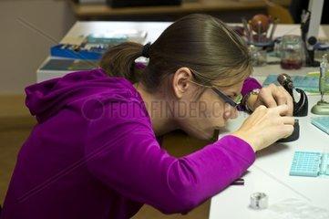 Hochkonzentrierte Uhrmacherin bearbeitet Einzelteile einer Armbanduhr  Motiers  Schweiz