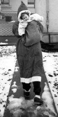 Kind auf Ruecken von Weihnachtsmann