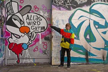 Junge  12 Jahre  zeigt auf eine Graffiti  Deutschland  Europa