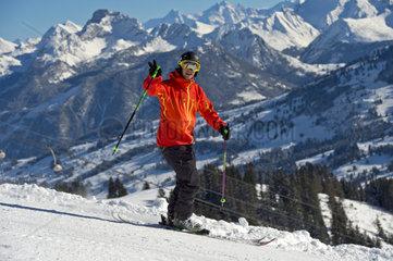Skifahrer grss sst auf einer Skipiste vor der Bergkulisse der Berner Alpen  Skigebiet Schoenried  Saanenland  Kanton Bern  Schweiz