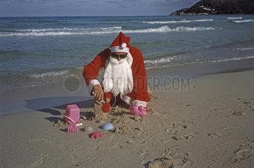 Weihnachtsmann spielt am Strand