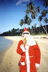 Weihnachtsmann isst Banane am Strand