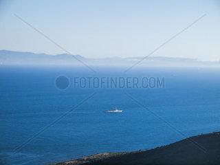 Blick von Spanien ueber die Strasse von Gibraltar nach Marokko. Unbekanntes Kriegsschiff in der Stasse von Gibraltar