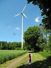 Kind auf einem Feldweg vor einem Windrad
