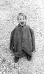 Kind in grossem Mantel lacht