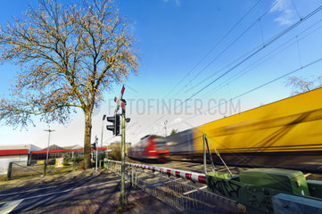 Personenzug und Gueterzug begegnen sich an einem Bahnuebergang
