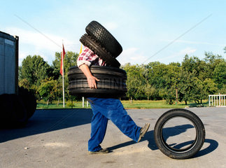 Mechaniker traegt Reifen