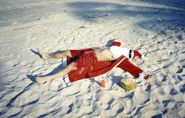Weihnachtsmann liegt am Strand