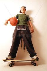 Junge mit Basketball und Skateboard