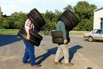 zwei Maenner tragen viele Reifen