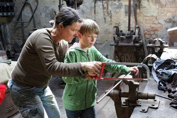 Cammin  Deutschland  Frau hilft einem Jungen beim Zersaegen einer Eisenstange