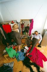 Mann schlaeft ein neben Frau bei der Kleiderwahl