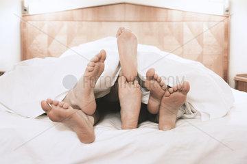 drei paar Fuesse in einem Bett