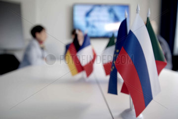 Blur effect. Meeting of management  meeting of directors. International commission  table with flags of EU  Russia and other countries
