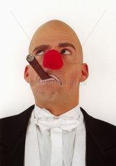 Clown in Anzug und mit roter Nase und Zigarre