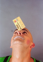 Mann jongliert mit goldener Kreditkarte