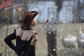 Berlin  Deutschland  Junge blaest Flugsamen eines Rohrkolben in die Luft