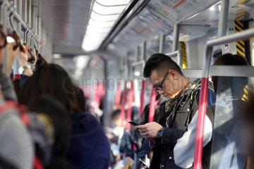 Hong Kong  China  Mann schaut in einem U-Bahnabteil auf sein Smartphone