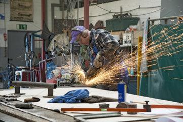 Handwerker arbeitet mit einem Trennschleifer in seiner Werkstatt