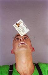 Clown balanciert Personalausweis auf der Nase