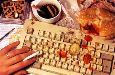 Man isst Hamburger ueber Tastatur