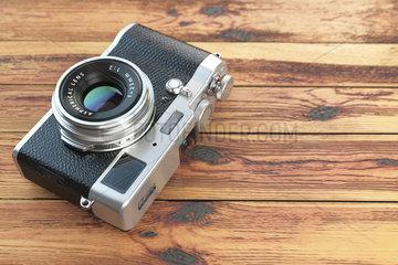 Modern mirrorless camera stilized to retro vintage film camera on wood table background.