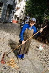 Berlin  alter Mann fegt den Gehweg