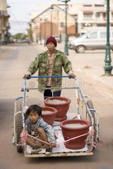 Laote faehrt Blumentoepfe und seinen Sohn auf einem Handkarren durch die Stad