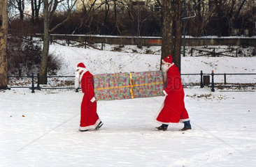 Weihnachtsm__nner tragen Riesenpaket