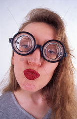 Blonde Frau mit dicker Brille macht Kussmund