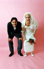 Hochzeitspaar schneidet Grimassen