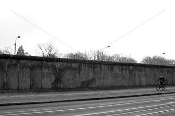 Berlin  Deutschland  Radfahrer faehrt an einem Teil der ehemaligen Grenzmauer vorbei