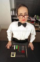 Sekretaerin mit dicker Brille am sauberen Schreibtisch