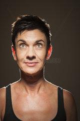 laechelnde schwarzhaarige Frau blickt nach oben vor Schwarz