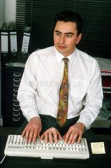 Mann mit drei Haenden an Tastatur