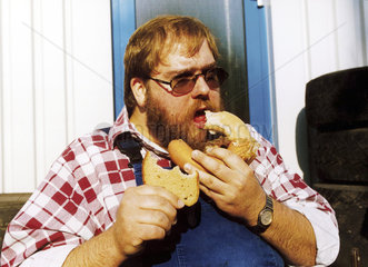 fetter Mann isst Fleischwurst