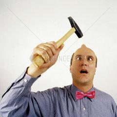 Mann schlaegt sich mit Hammer auf den Kopf