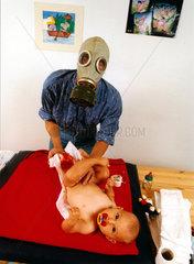 Mann mit Gasmaske wickelt Baby