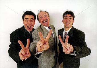 Drei Maenner zeigen Victory
