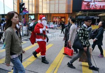 Hong Kong  China  Weihnachtsmann ueberquert eine belebte Strasse