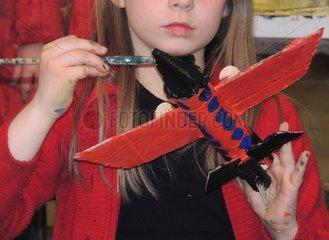 Maedchen bemalt selbstgebasteltes Flugzeug