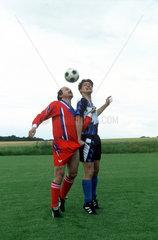 zwei Fussballer beim Kopfballduell