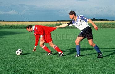 Fussballer zieht Gegner am Shirt