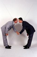 zwei Geschaeftsmaenner schuetteln die Haende und buecken sich