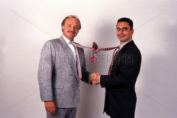 zwei Geschaeftsmaenner mit verknoteten Krawatten schuetteln die Haende