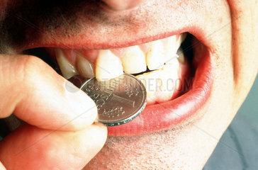 Mann beisst Geldstueck DM Deutsche Mark