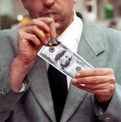 Mann zuendet sich die Zigarre mit Dollarschein an